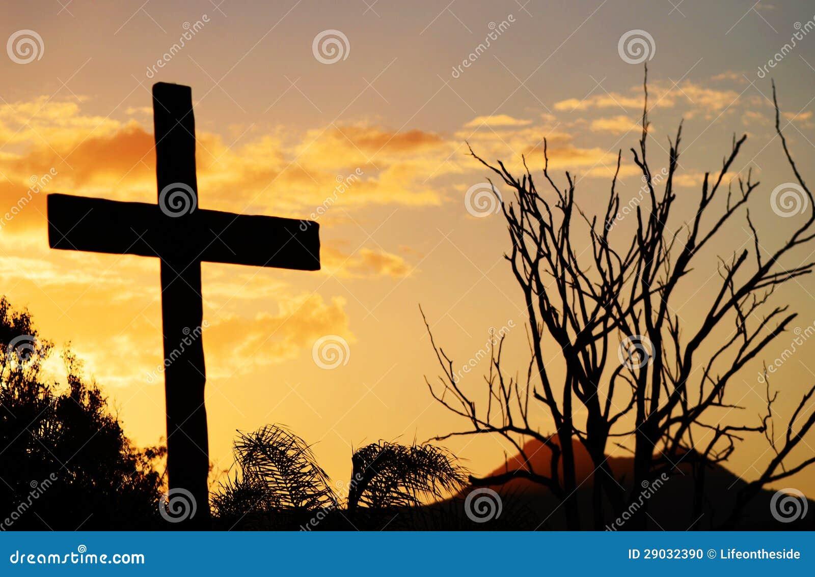 Крест спасения Христоса на холме на заходе солнца