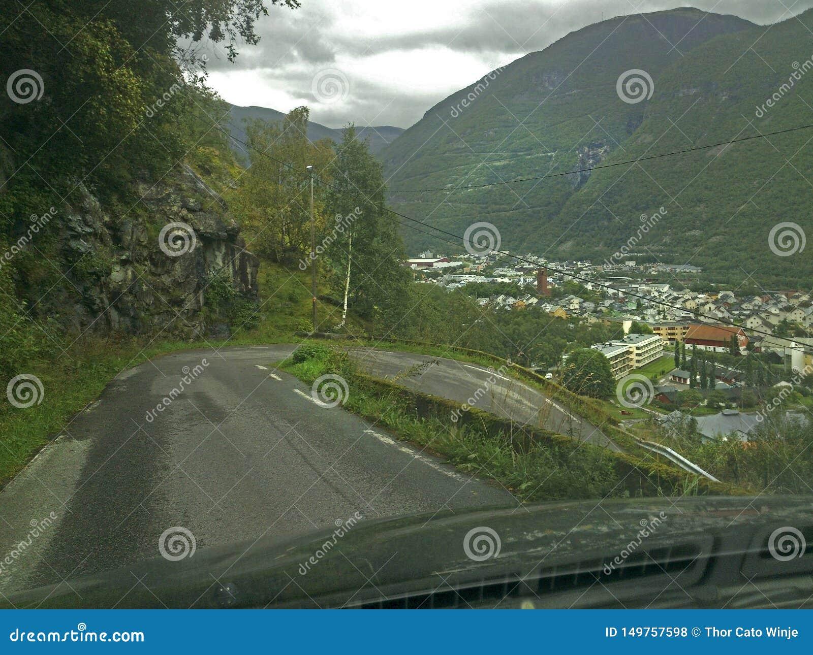 Кривая Hairpin на крутой дороге сфотографированной изнутри автомобиля через ветровое стекло
