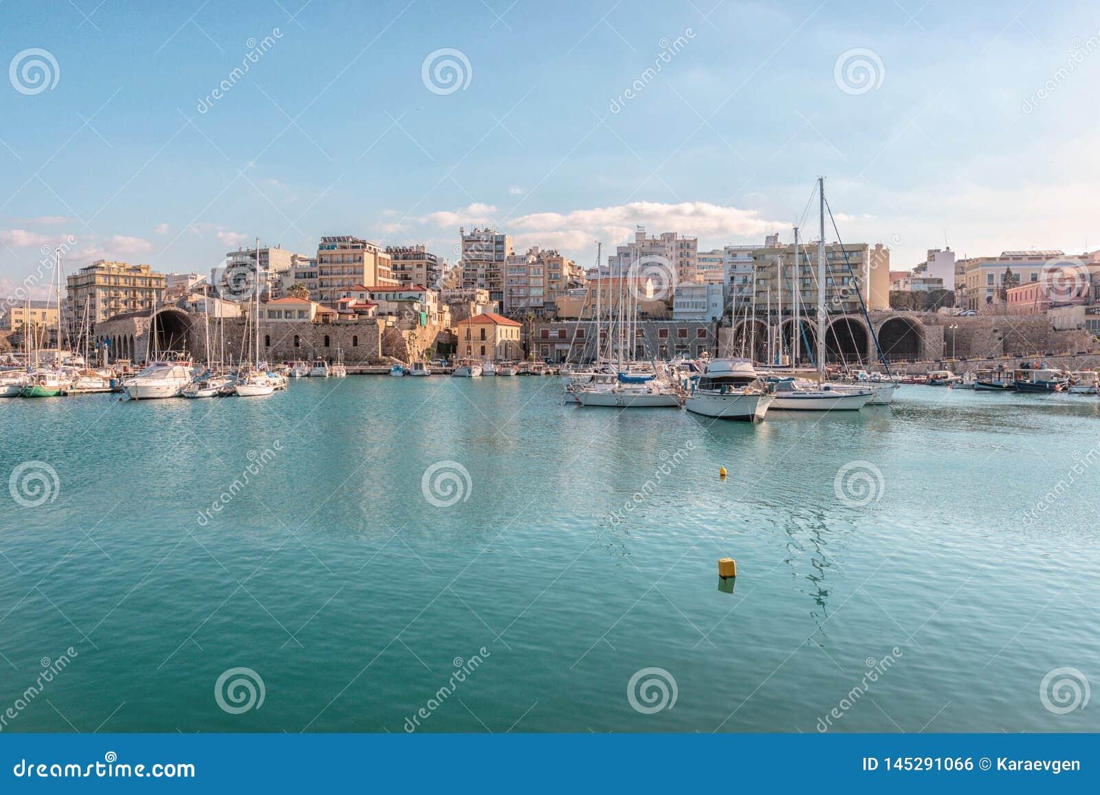 Крит, Греция - 11-ое февраля 2019: Шлюпки и яхты в порте на предпосылке города ираклиона Греция