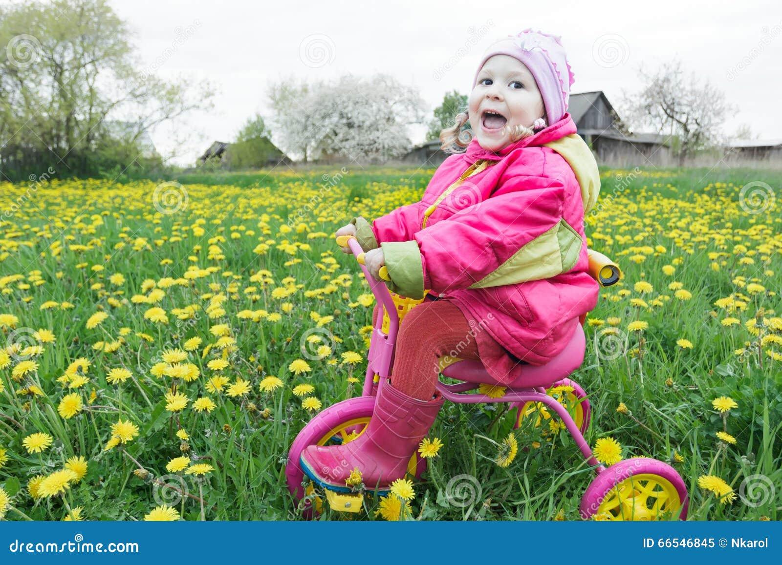 Крича маленькая девочка управляя розовым и желтым циклом через луг одуванчиков весны blossoming
