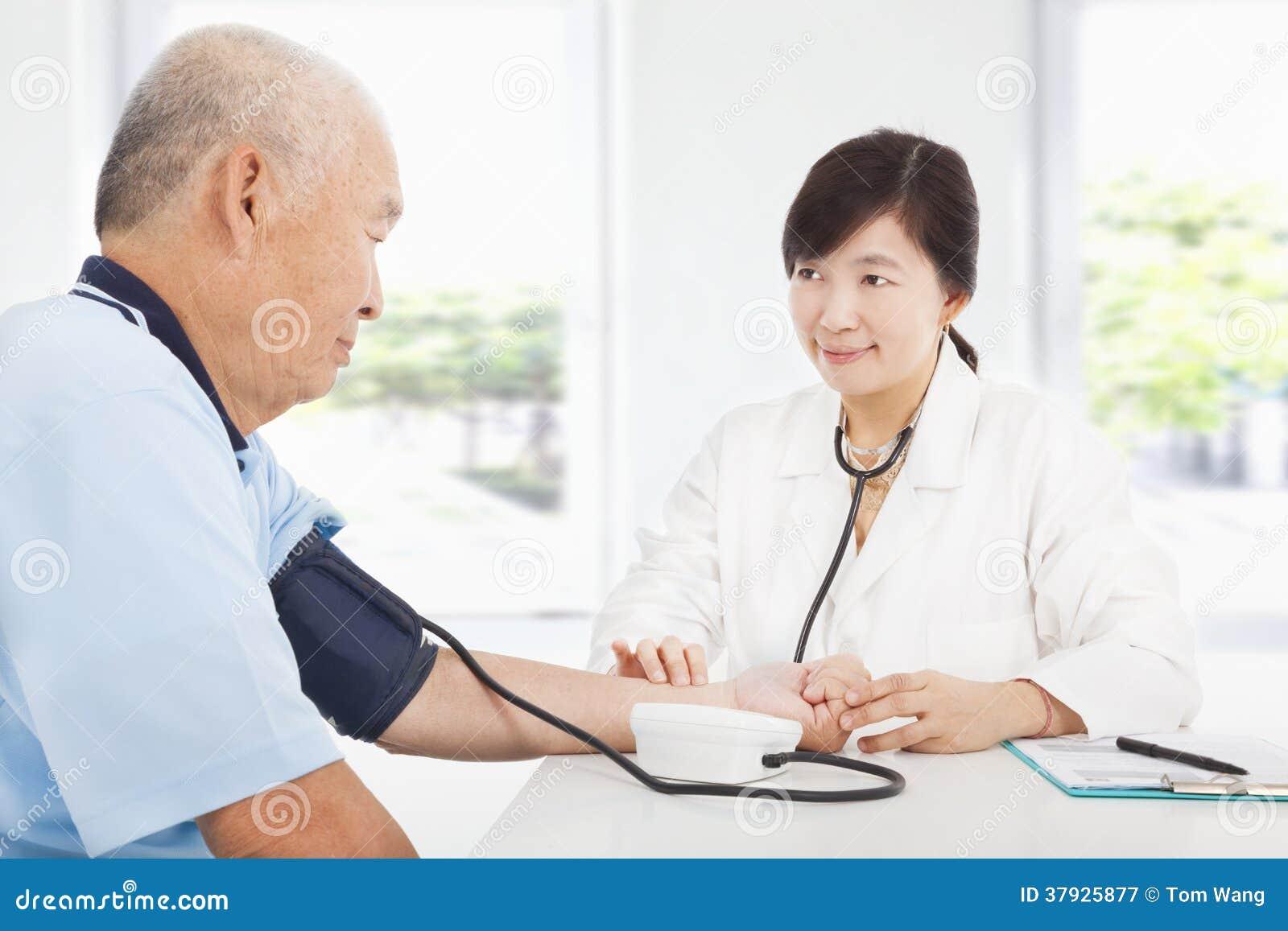 Кровяное давление доктора измеряя старшего человека