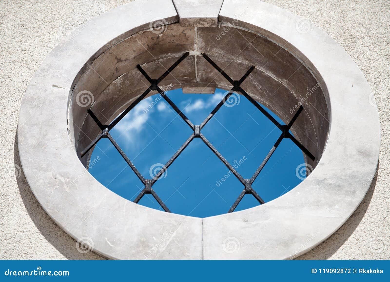 Круглое средневековое окно с взглядом голубого неба баров - абстрактной предпосылкой концепции - внутри помещения Outdoors концеп