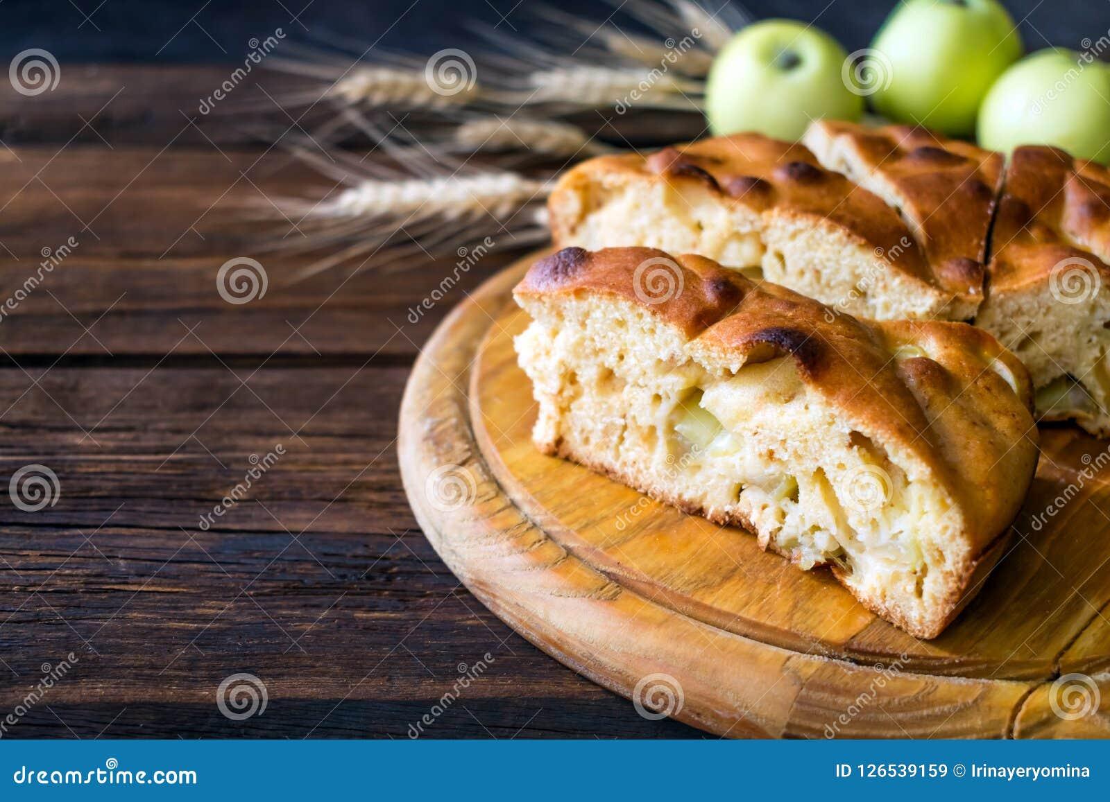 Круглый самодельный яблочный пирог, сапожник, коричневое Бетти, Яблоко Шарлотта на деревянной предпосылке с яблоками