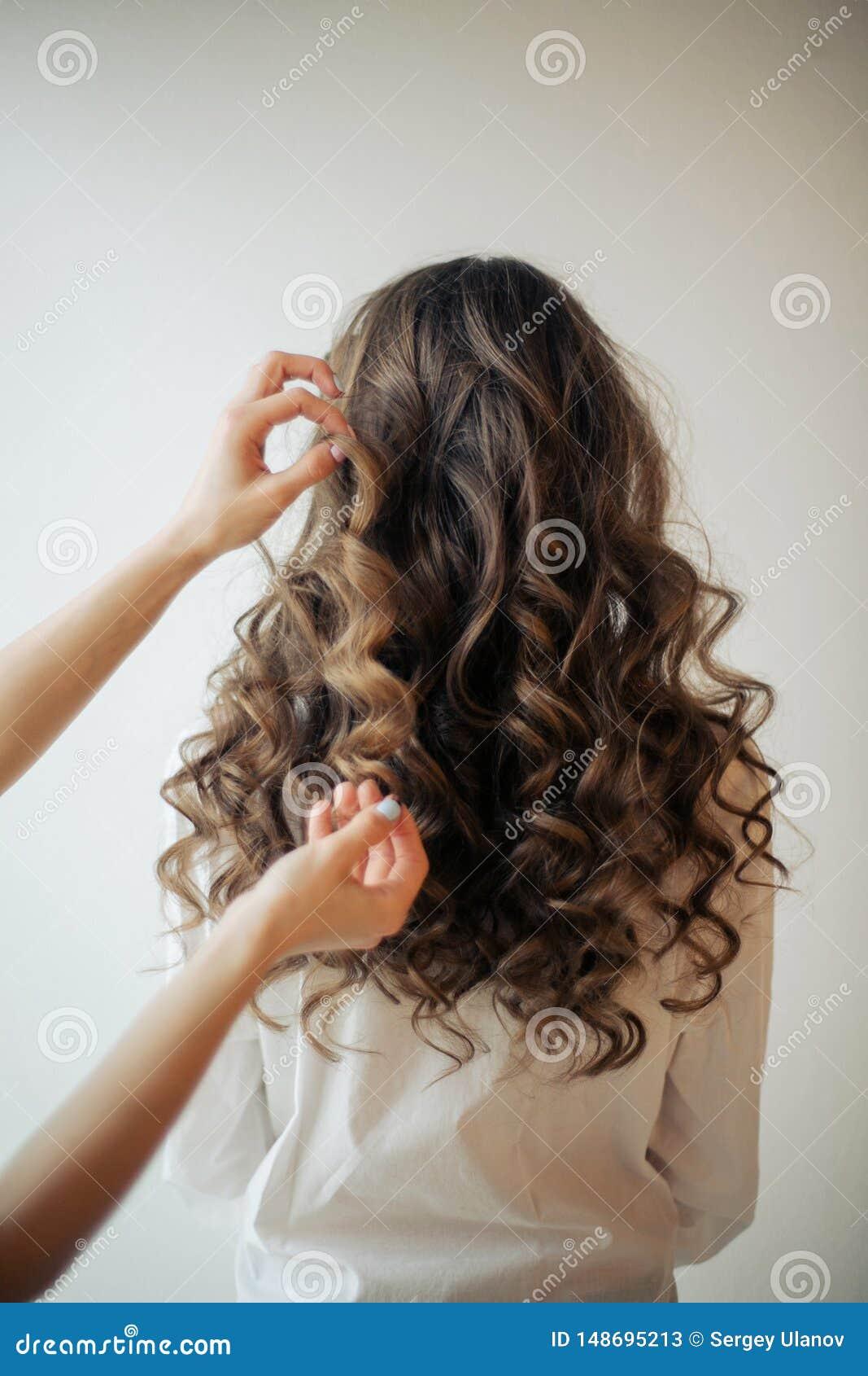 Крупный план женских рук парикмахера или coiffeur делает стиль причесок