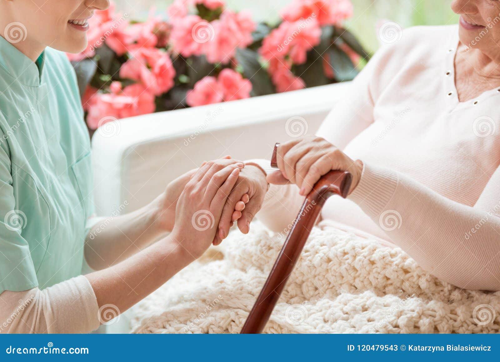 Крупный план заботя волонтера работая в holdi дома престарелых