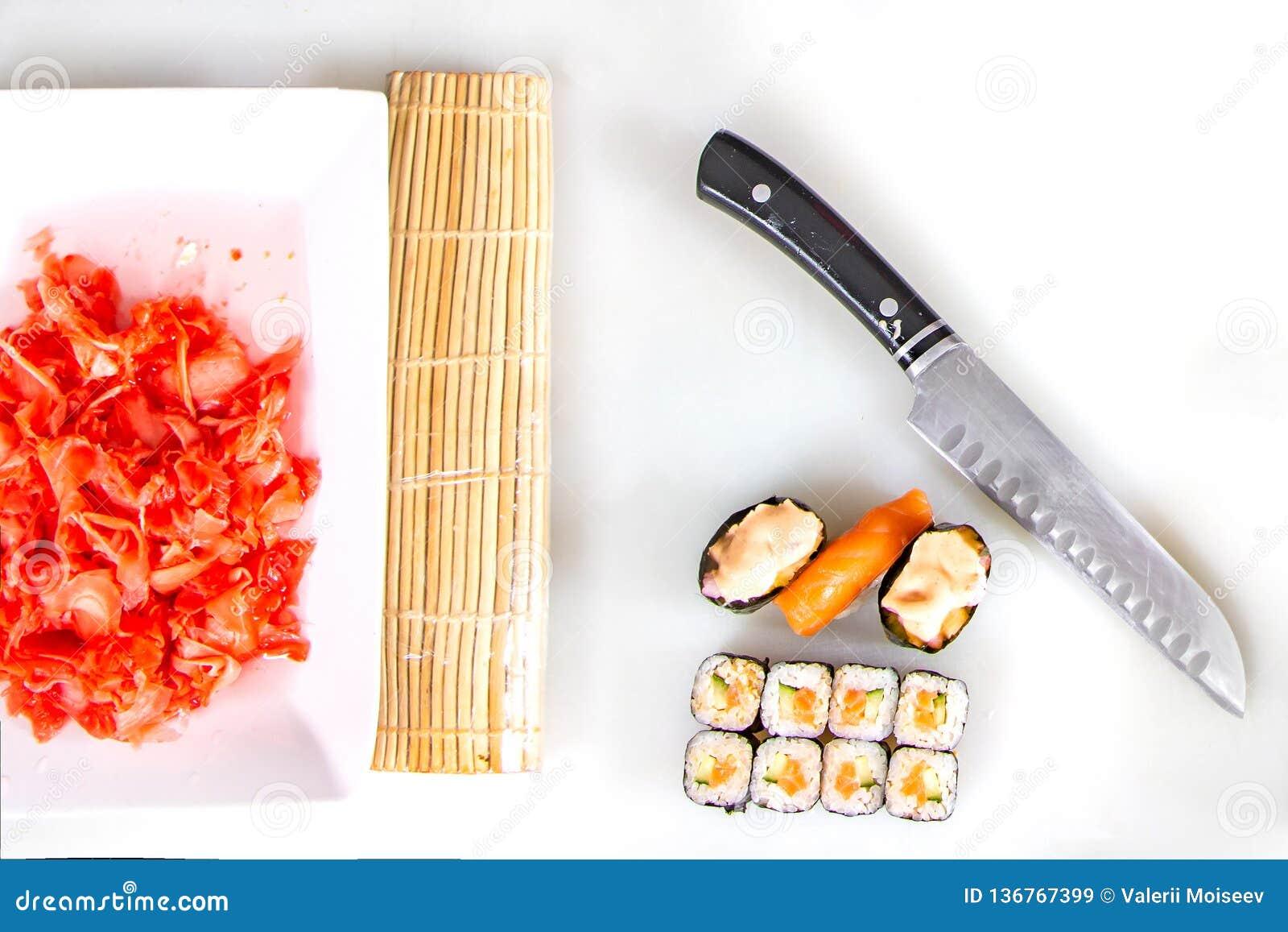 Крупный план завальцовки вверх по сушам на кухне с ножом и ингредиентами