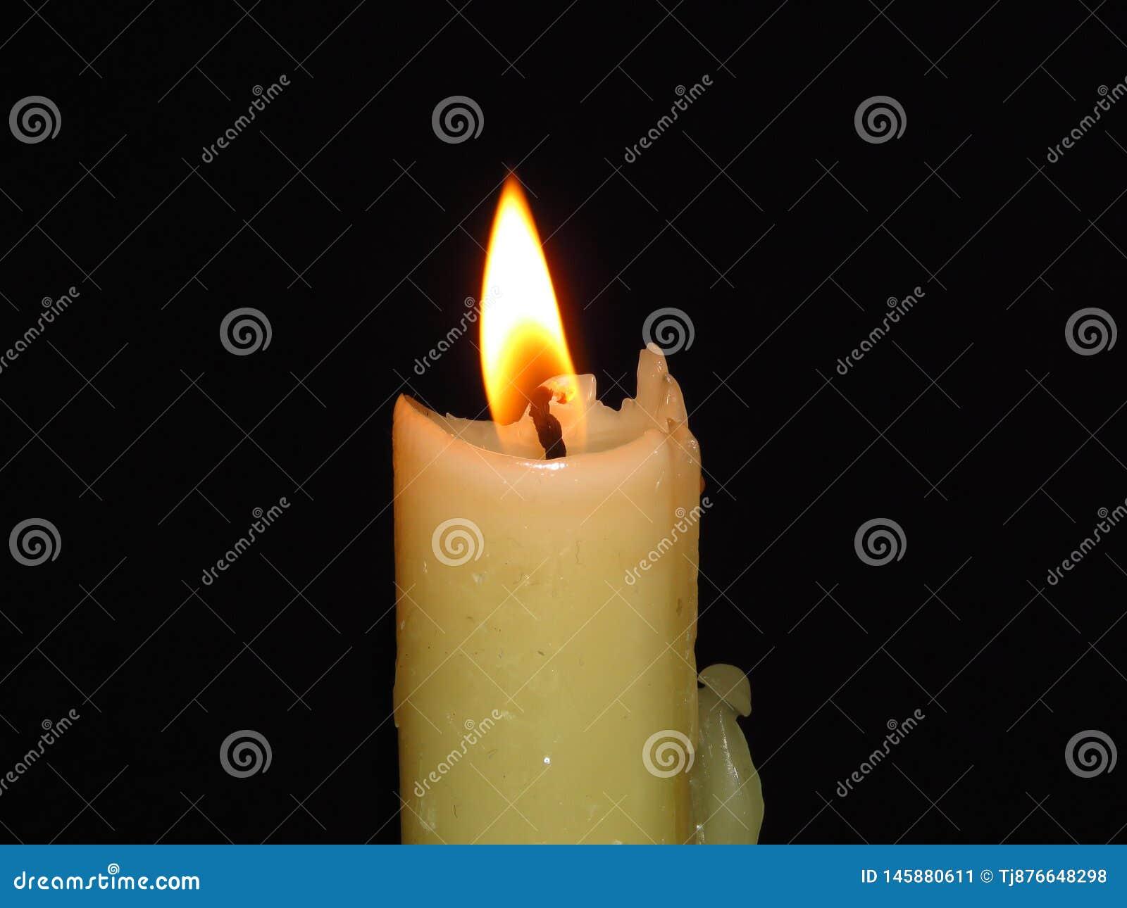 Крупный план изолированной горящей свечи на темной черной предпосылке Пламя, свет, воск свечи Тайна, концепция вероисповедания