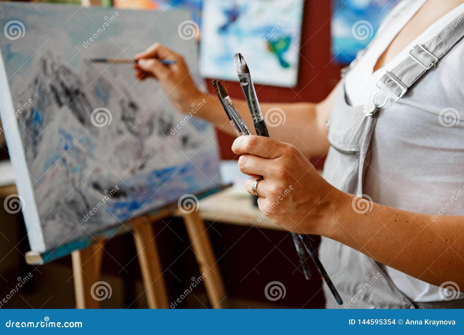 Крупный план картины чертежа художника женщины молодого красивого среднего возраста белой кавказской с акрилами на холсте