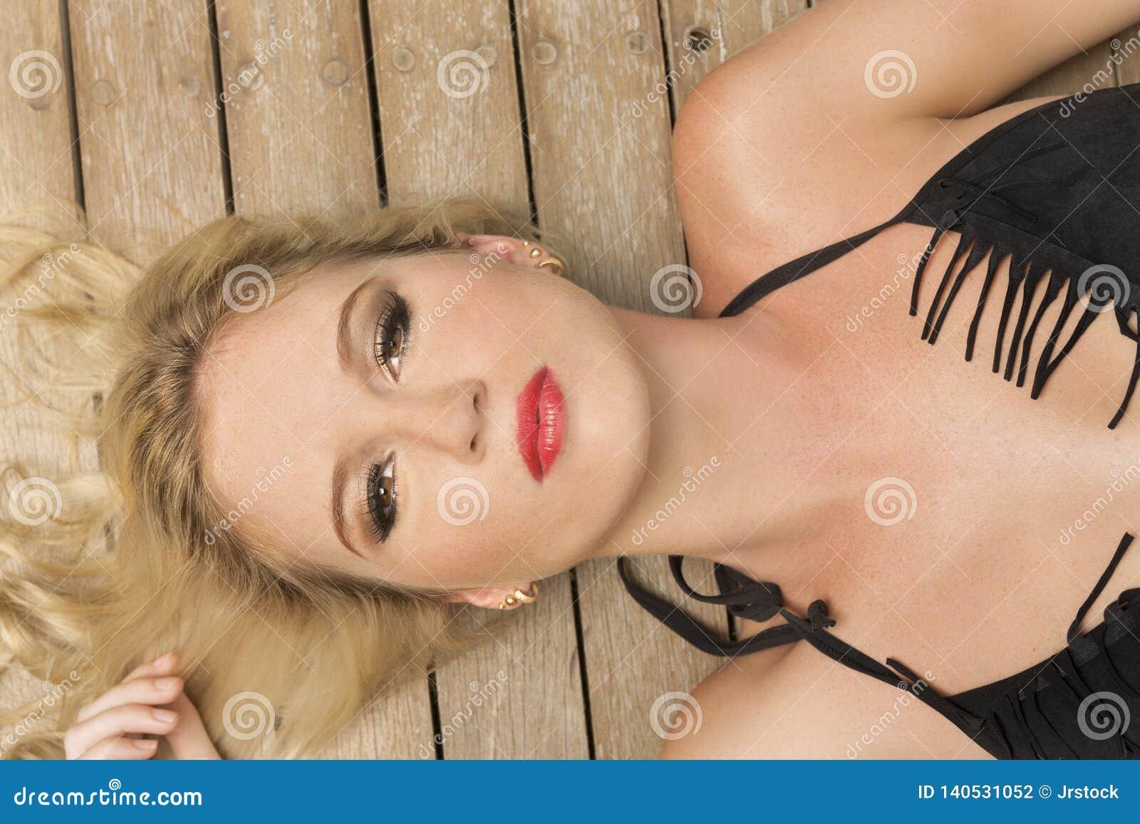 Крупный план красоты в черном бикини фокусируя ее сторону