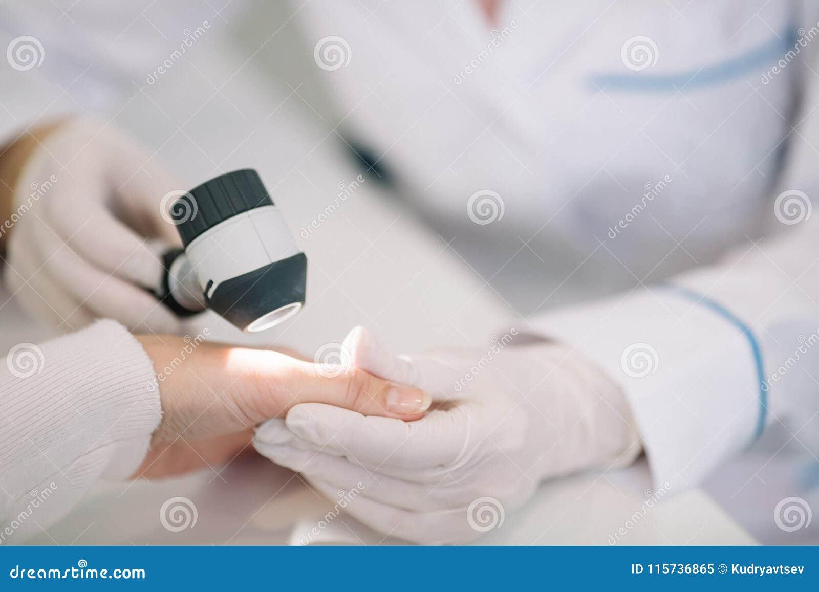 Крупный план моли дерматолога рассматривая в наличии женщины patien