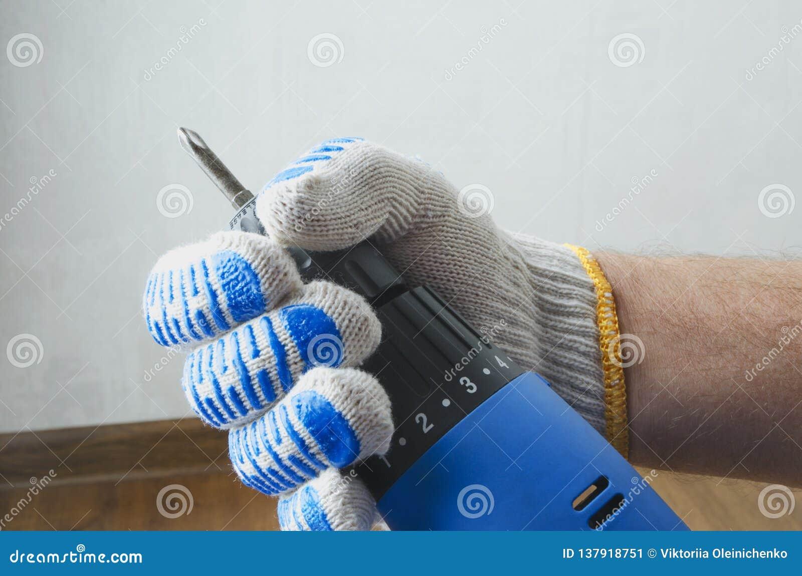 Крупный план мужской руки с голубой отверткой против белых стены и пола