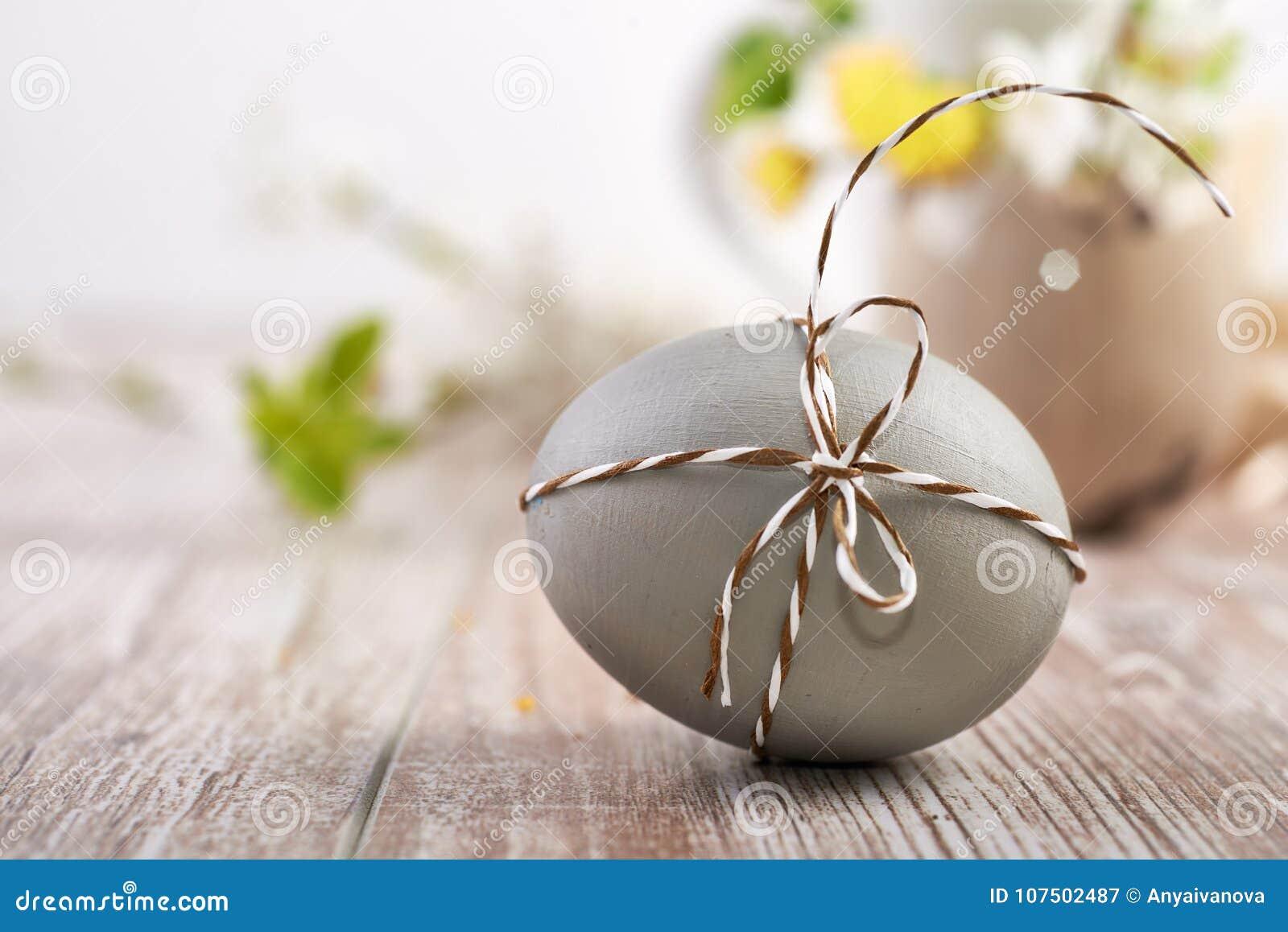 Крупный план на сером пасхальном яйце связанном с checkered шнуром на древесине