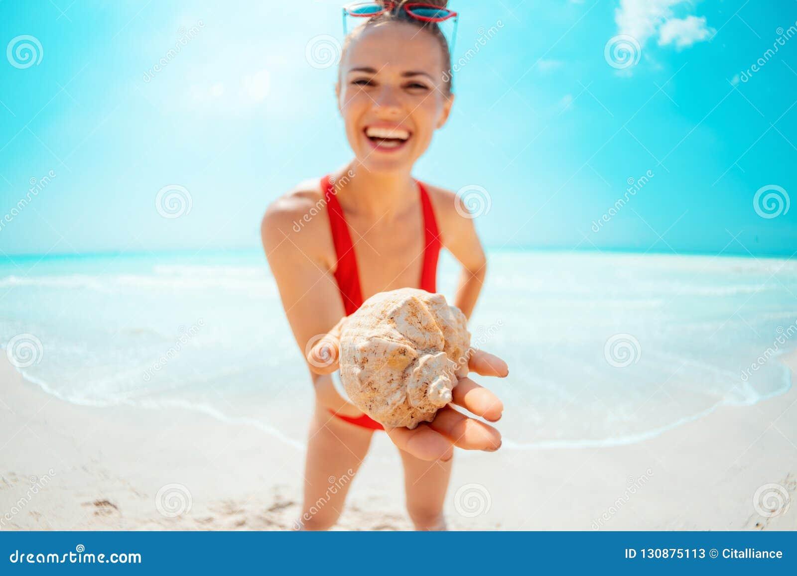 Крупный план на усмехаясь молодой женщине на раковине моря показа берега моря