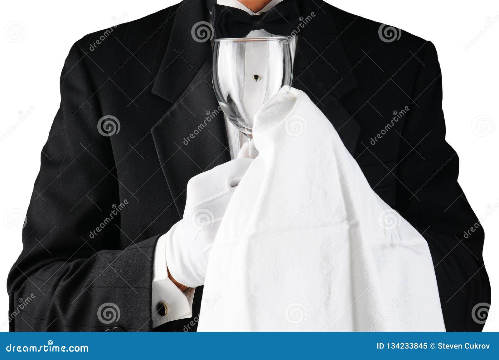 Крупный план официанта в смокинге полируя бокал