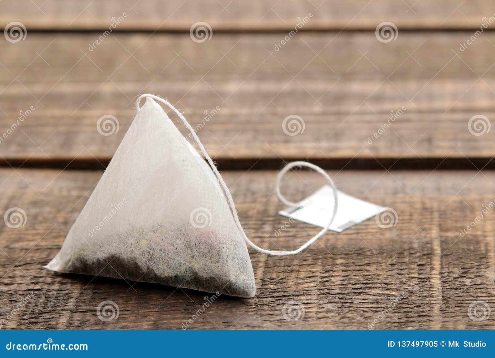 Крупный план пирамиды пакетика чая на коричневом деревянном столе Космос для текста