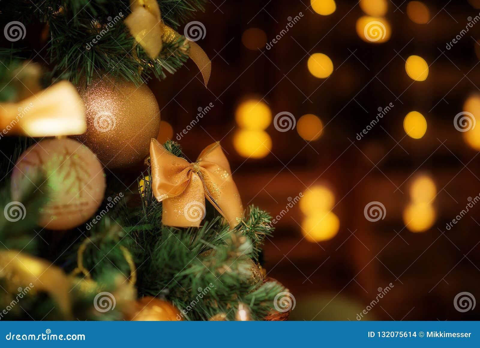 Крупный план рождественской елки с украшениями: золотые смычок и шарики Запачканные света на заднем плане Комната для текста экзе