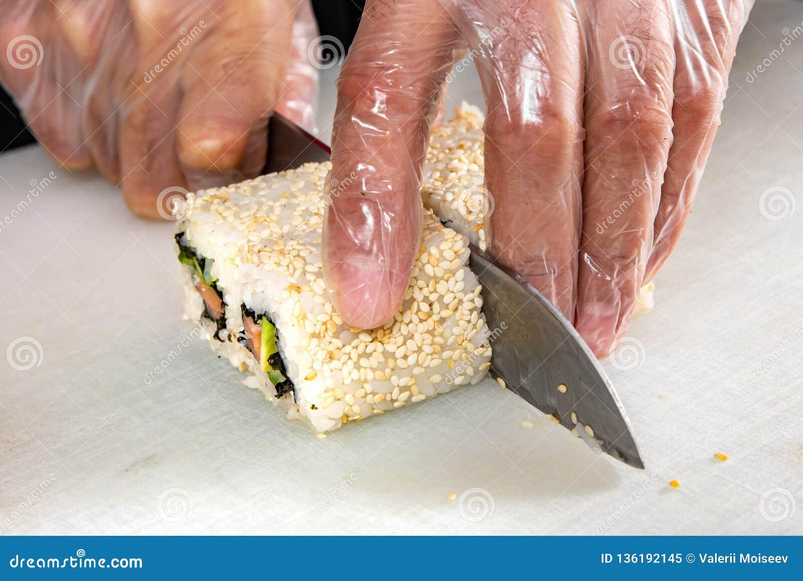 Крупный план рук шеф-повара свертывая вверх по отрезкам суш в части на кухне