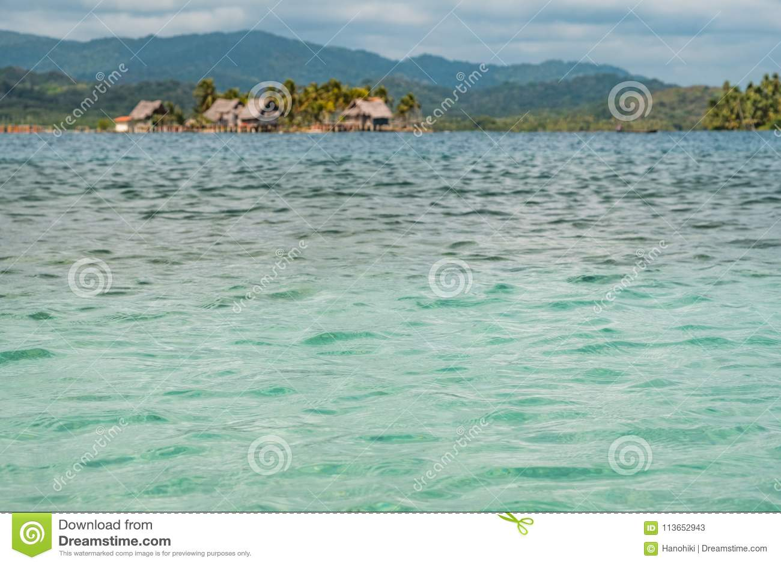 Крупный план текстуры воды океана с островом и деревянным backgr домов