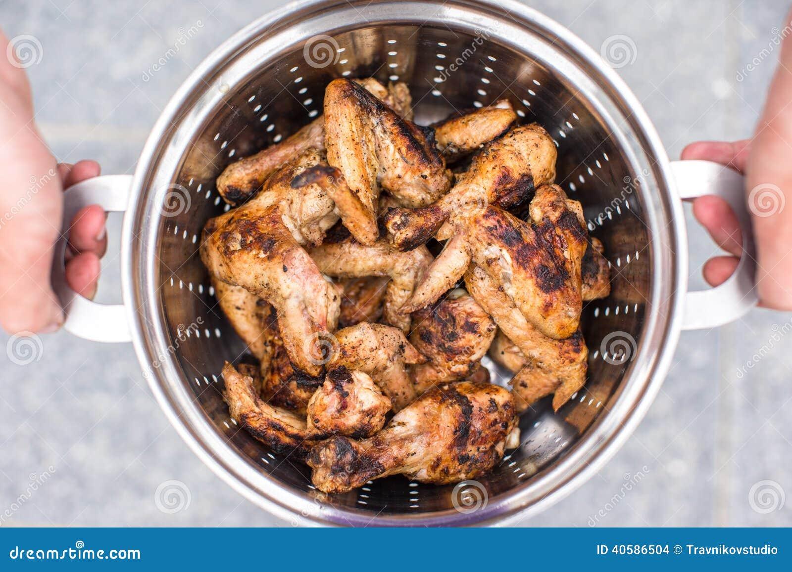 Крупный план зажаренного мяса в лоток металла в мужских руках