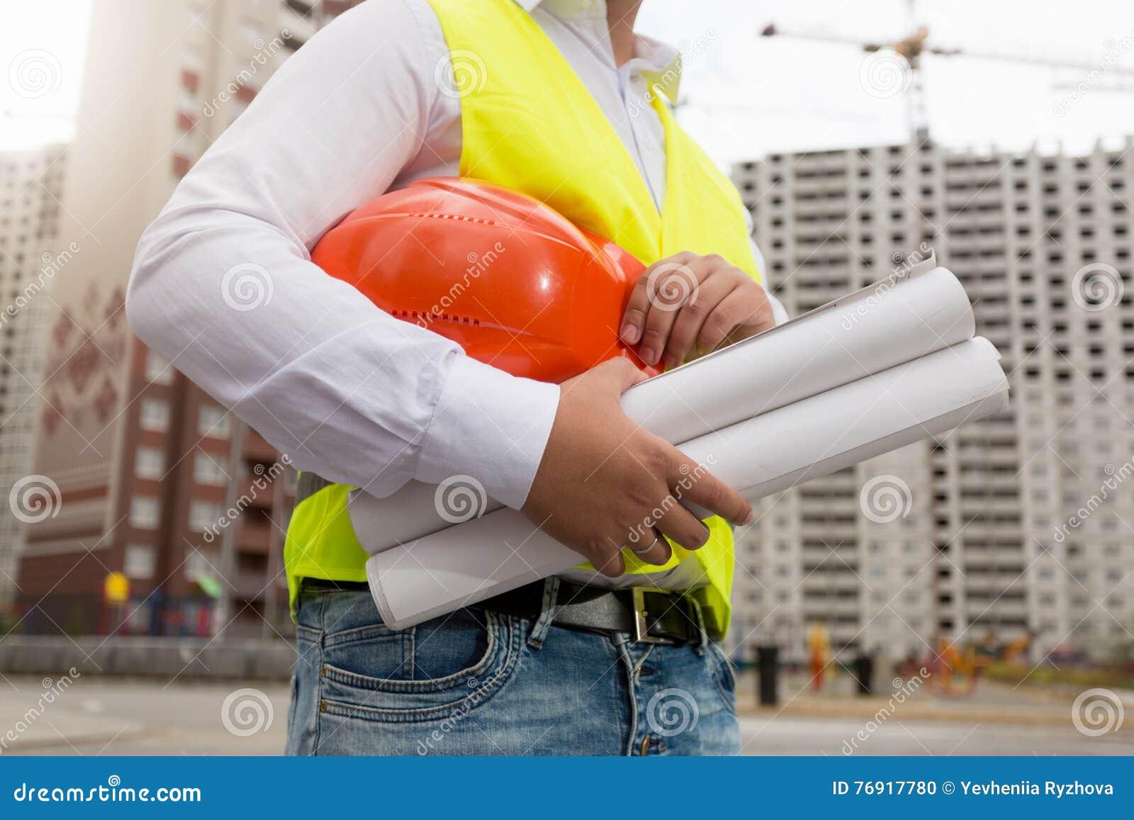 Крупный план молодого архитектора представляя с защитным шлемом и светокопиями дальше