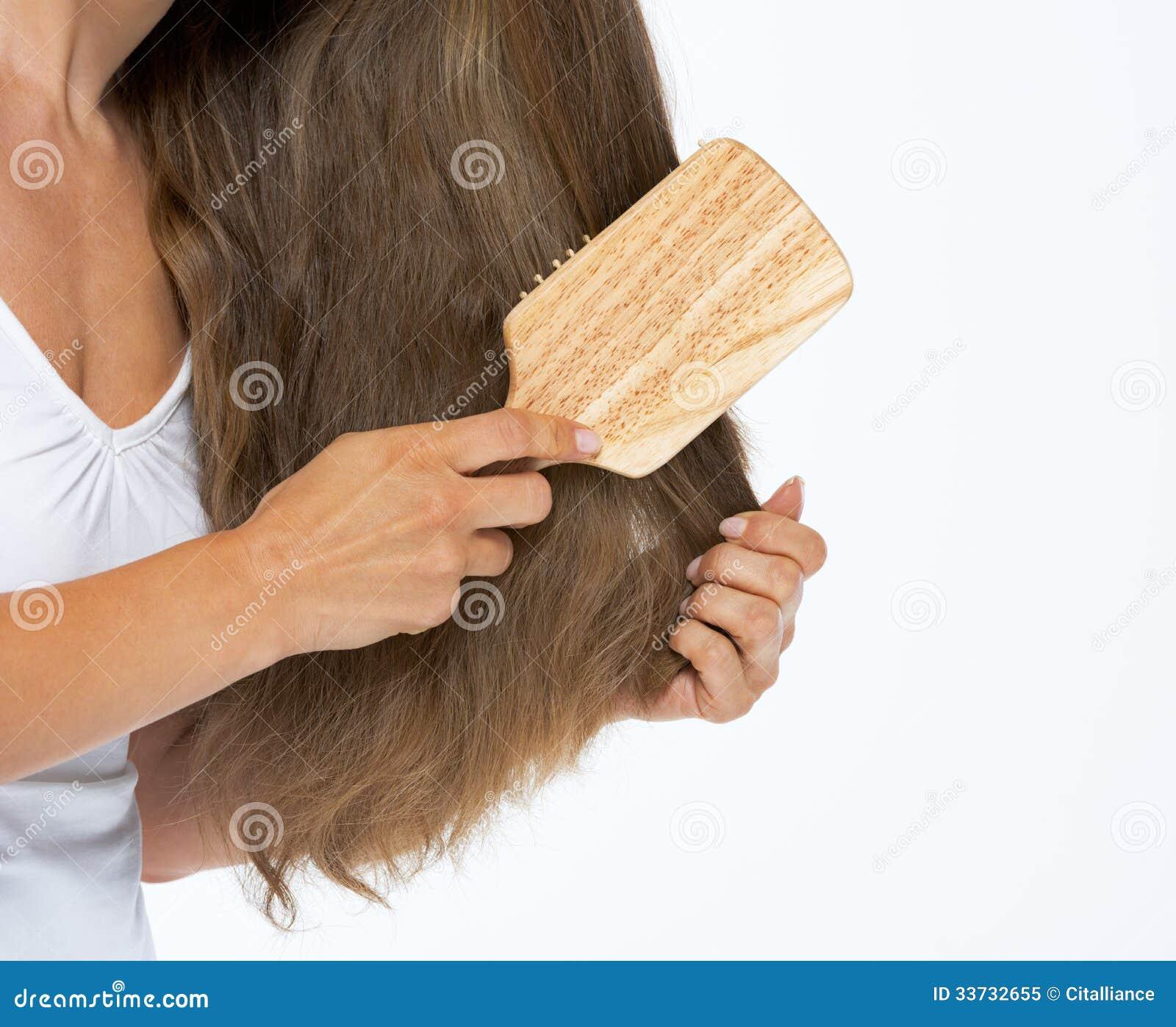 Крупный план на женщине расчесывая волосы