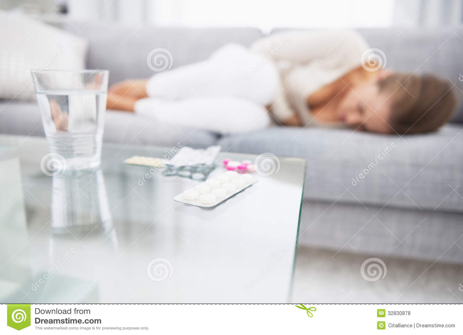 Крупный план на медицине на таблице и чувствуя плохой женщине в предпосылке