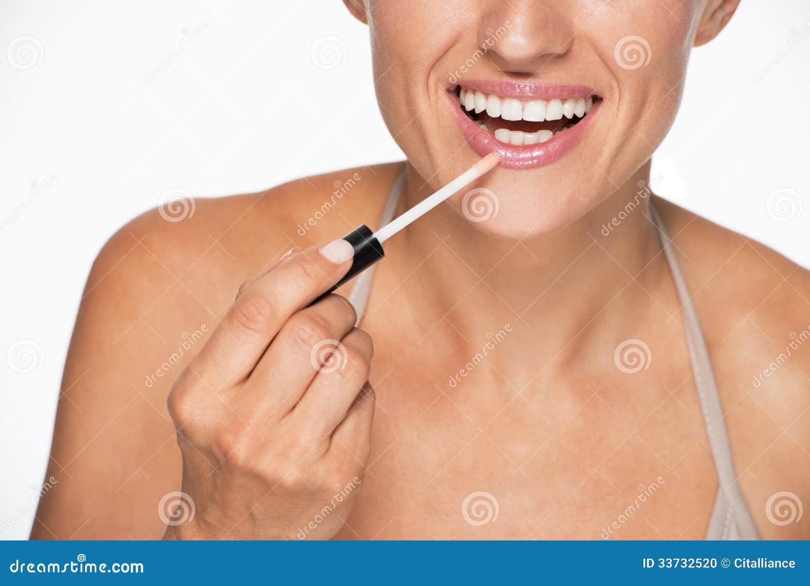 Крупный план на счастливой молодой женщине прикладывая лоск губы