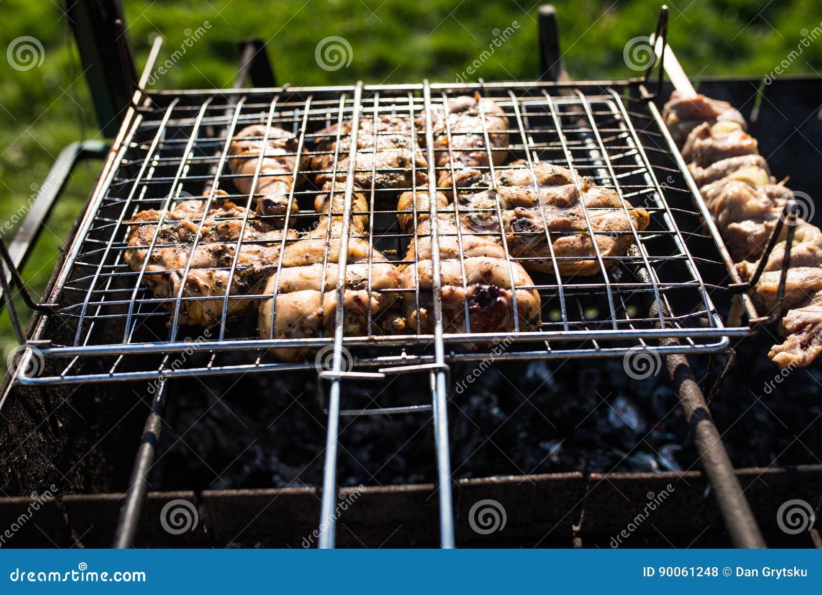 Крупный план некоторых протыкальников мяса будучи жаренным в барбекю Жарить marinated shashlik на гриле