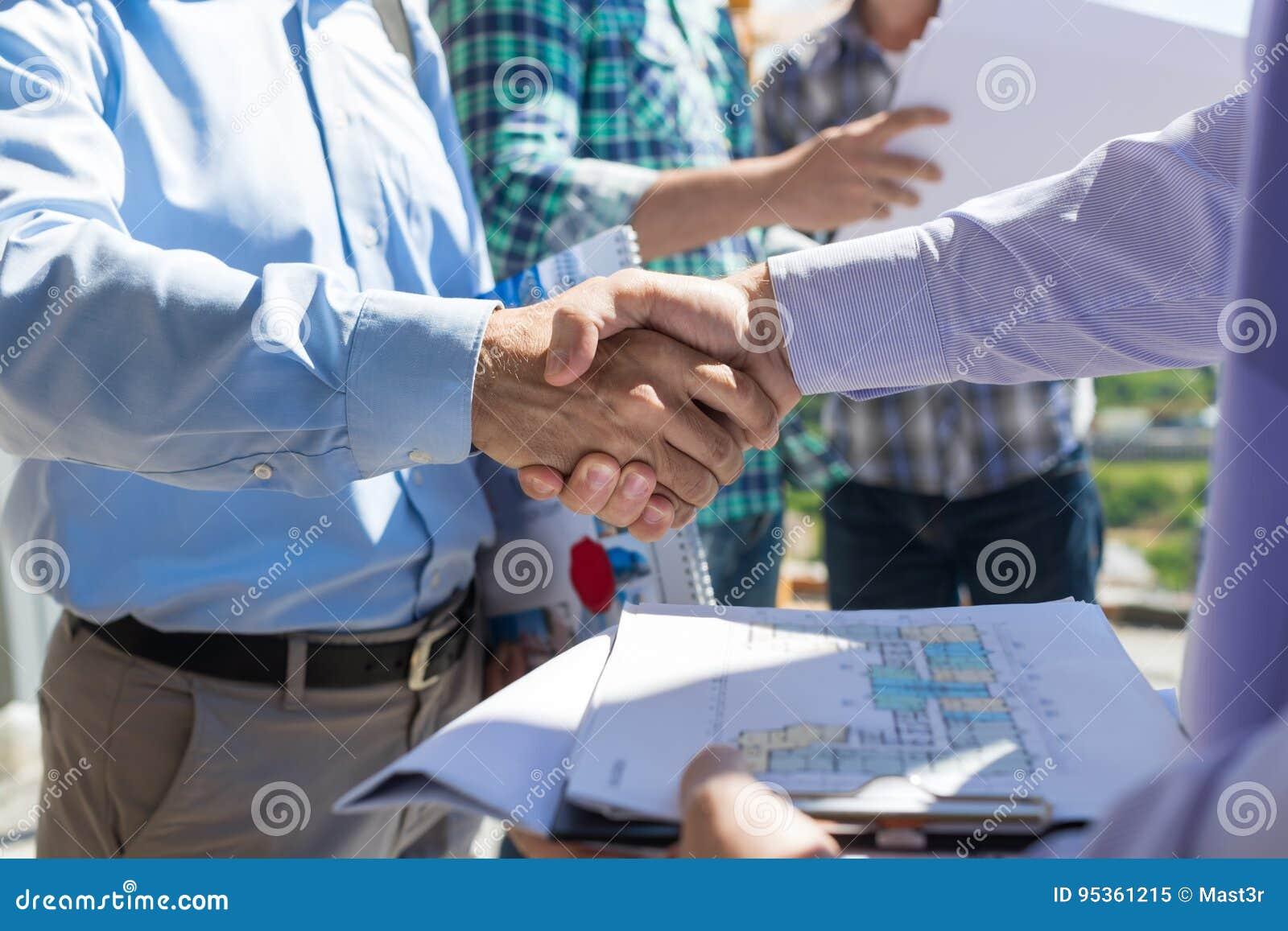 Крупный план рукопожатия построителей, 2 строя бизнесмена делая дело после обсуждения светокопии к новому проекту с