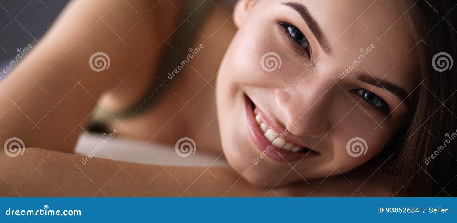 Крупный план усмехаясь молодой женщины лежа на кресле
