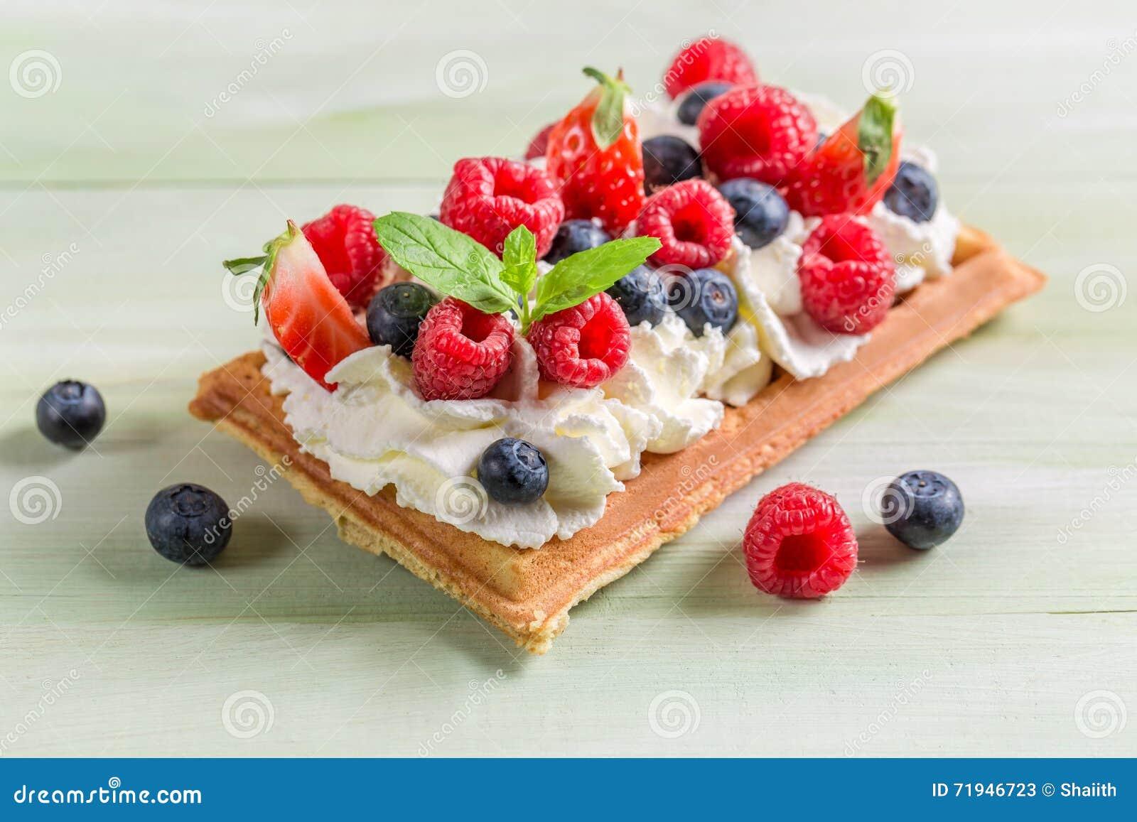 Крупный план waffle с плодоовощами ягоды и взбитой сливк
