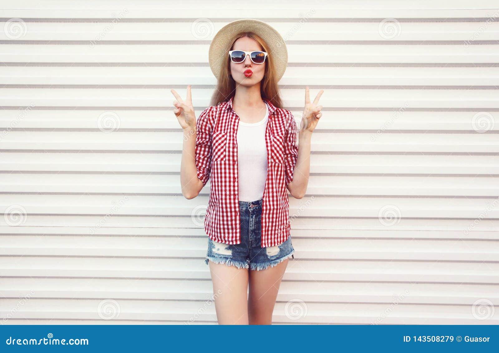 крутая девушка дуя красные губы отправляя сладкий поцелуй воздуха в соломенной шляпе круга лета, checkered рубашке, шортах на бел