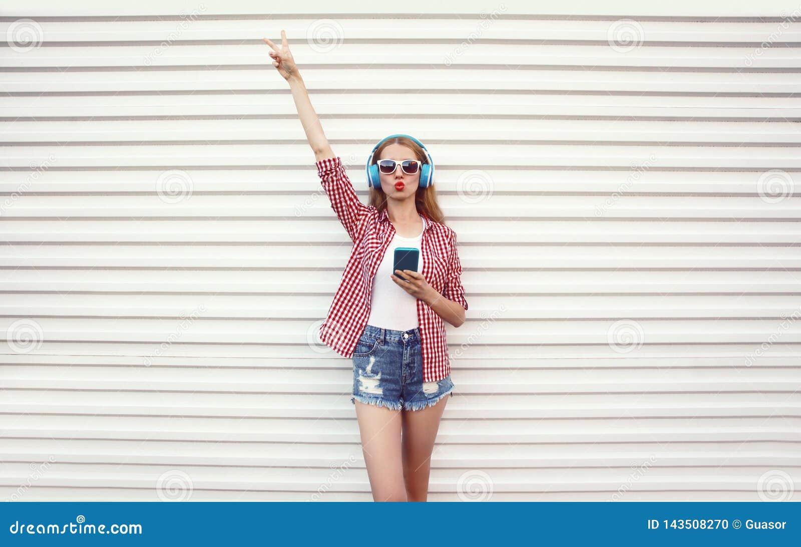 Крутая девушка поднимает ее руку вверх в наушниках со смартфоном слушая рубашку музыки нося checkered, шорты представляя на белой