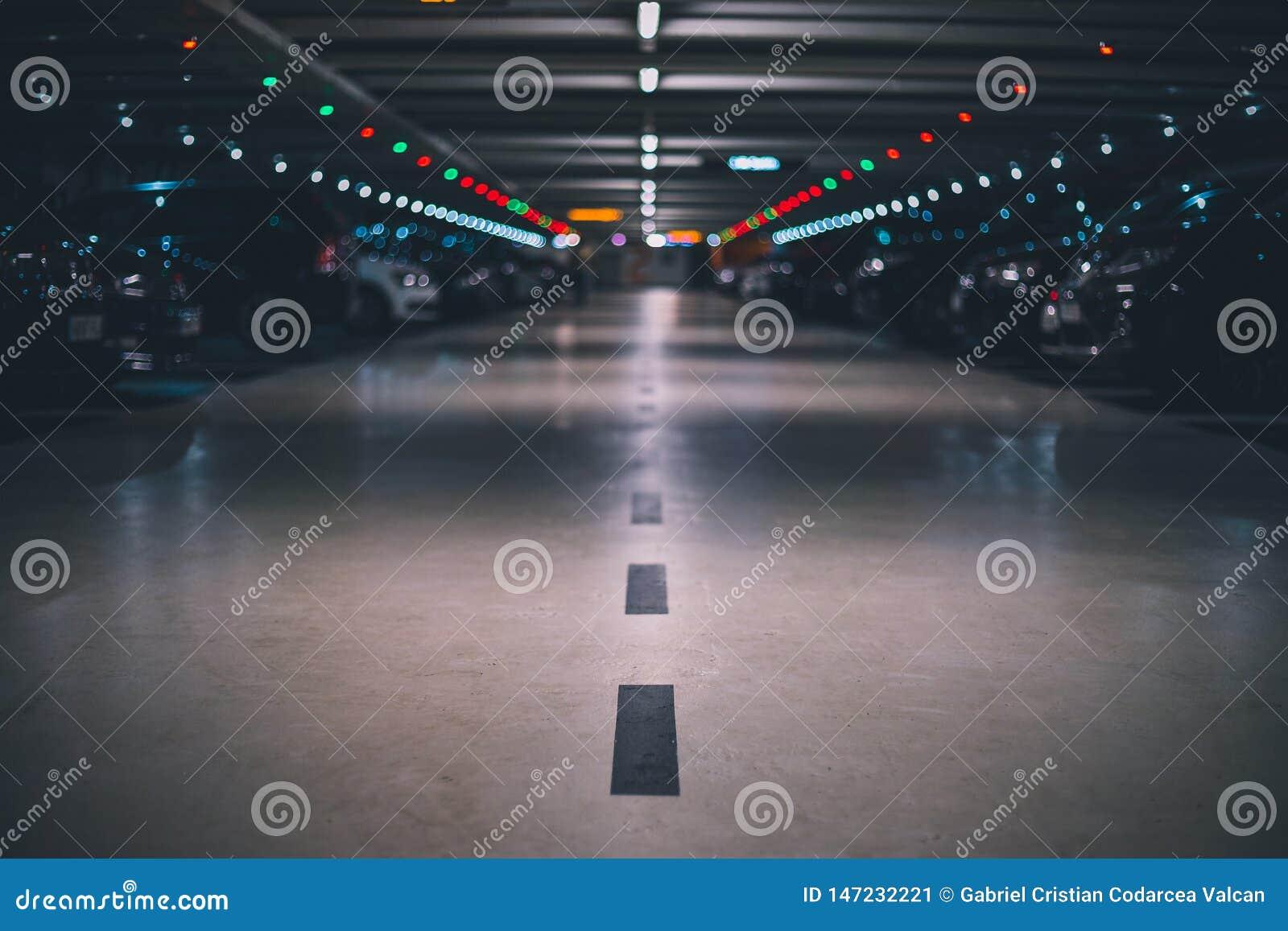 Крытая подземная парковка с запачканной съемкой и перспективой предпосылки низкой