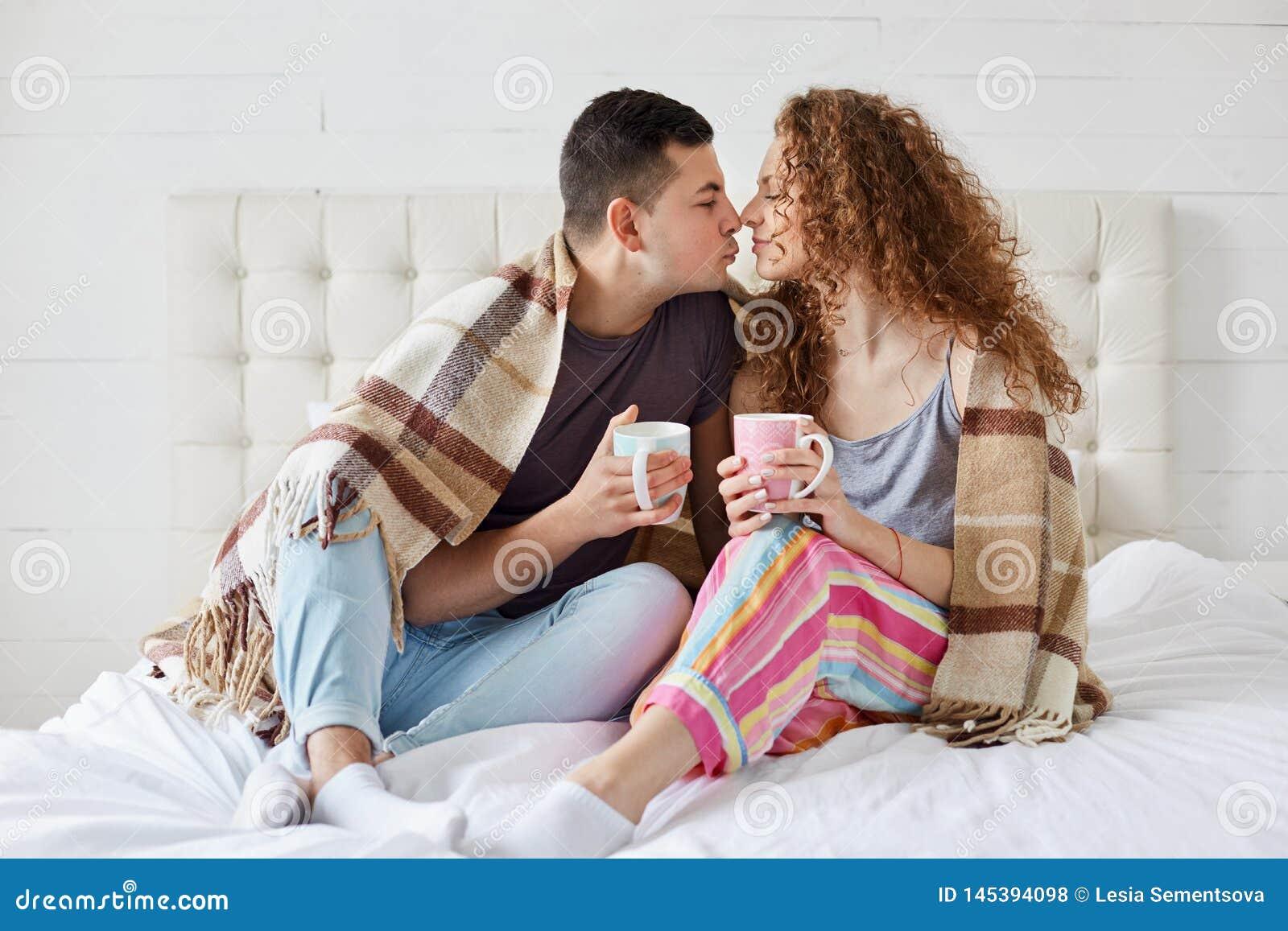 Крытая съемка счастливые женского и мужской имеет романтичные отношения, кофе напитка или чай, покрытые с шотландкой в спальне Ро