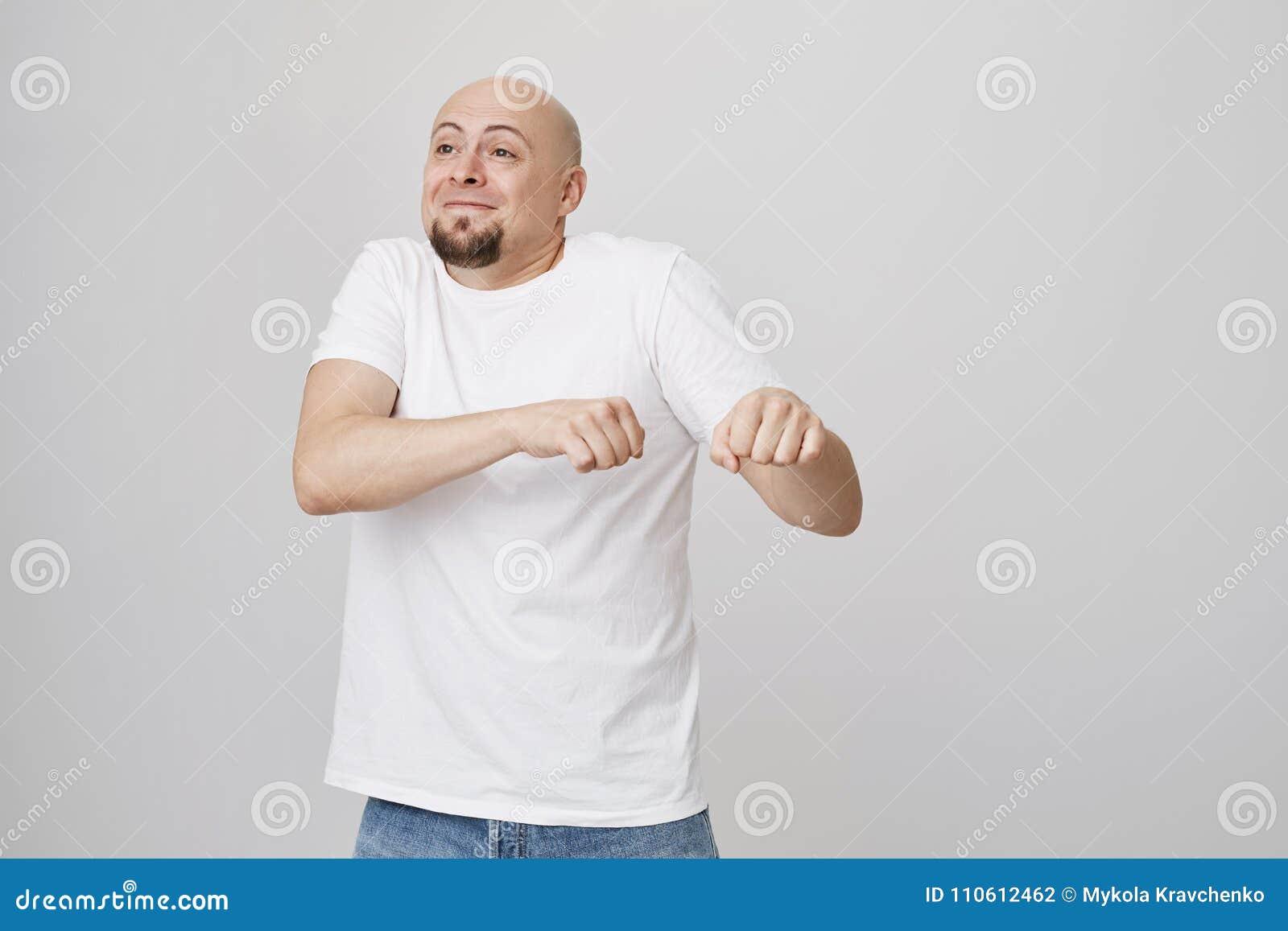 Крытый портрет смешного excited облыселого кавказского парня делая движение танца если празднующ что-то, находящся в большом наст