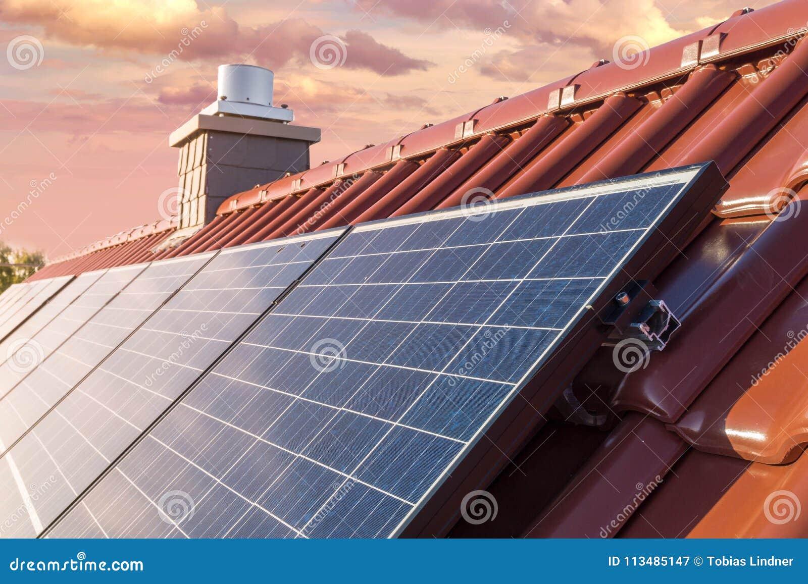 Крыша дома с панелью солнечных батарей или фотовольтайческой системой