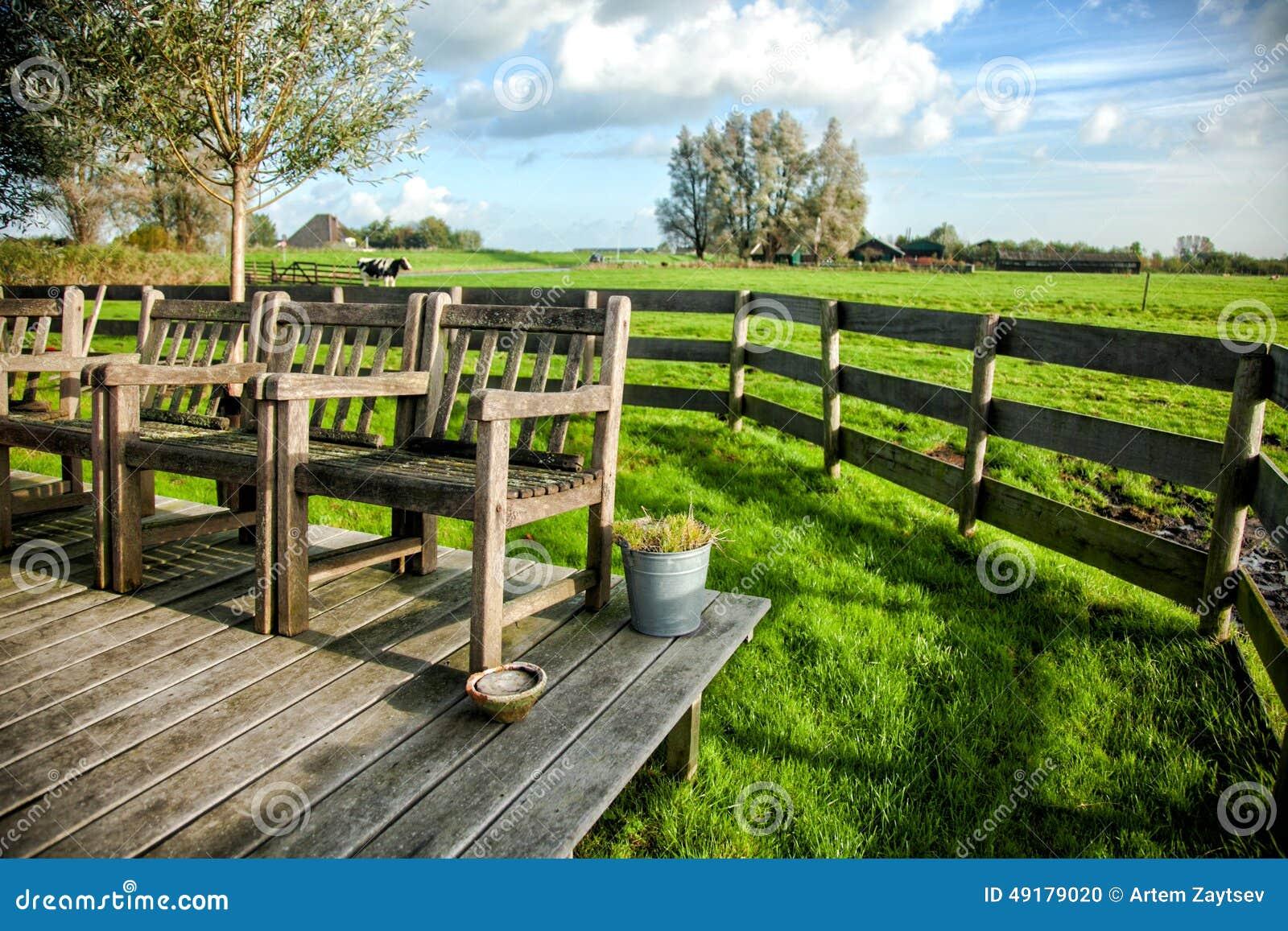 Крылечко сельского дома с винтажными стульями против