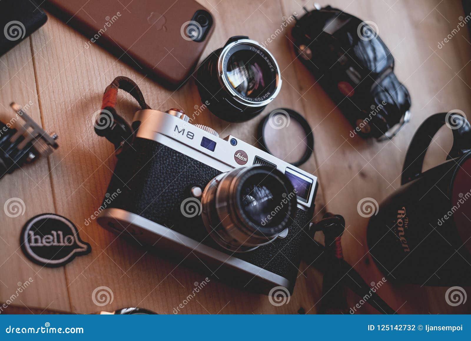 Куала-Лумпур, Малайзия - 30-ое августа 2018: Изображение натюрморта цифровой фотокамера и объектива Leica M8 на деревянном столе