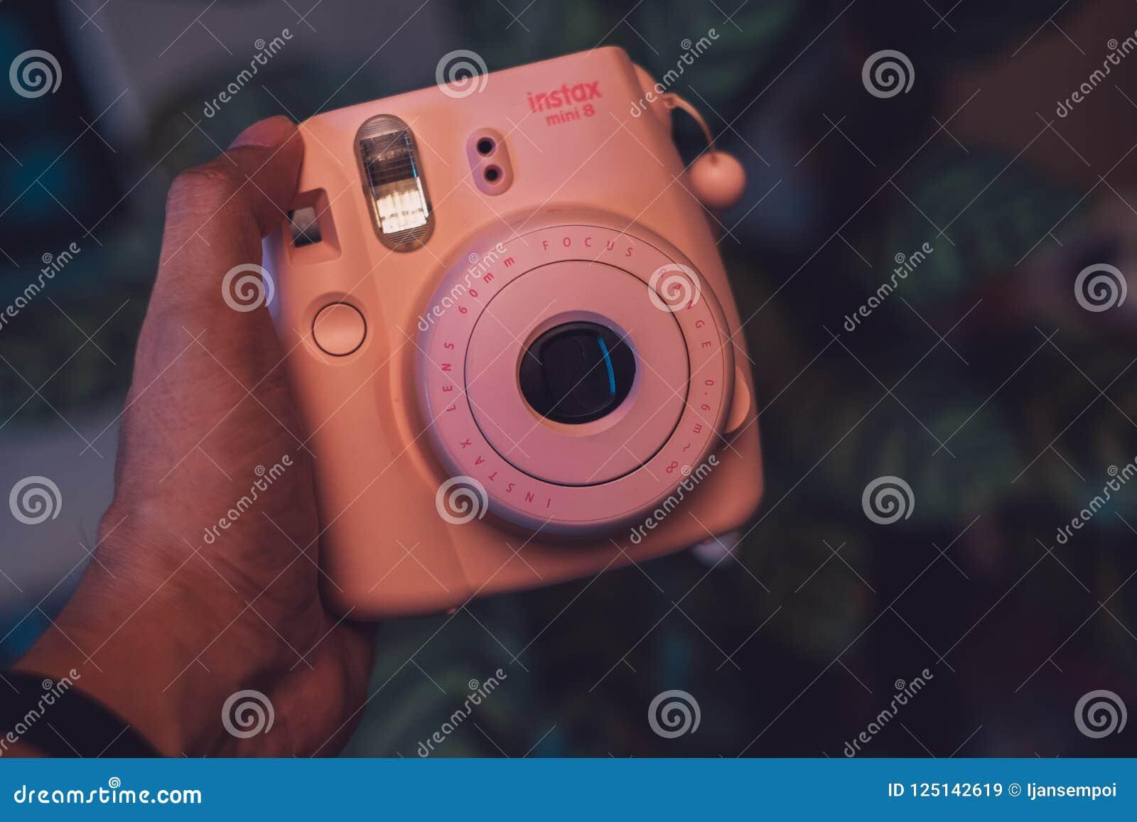 Куала-Лумпур, Малайзия - 31-ое августа 2018: Рука держа камеру Fujifilm поляроидную розовую