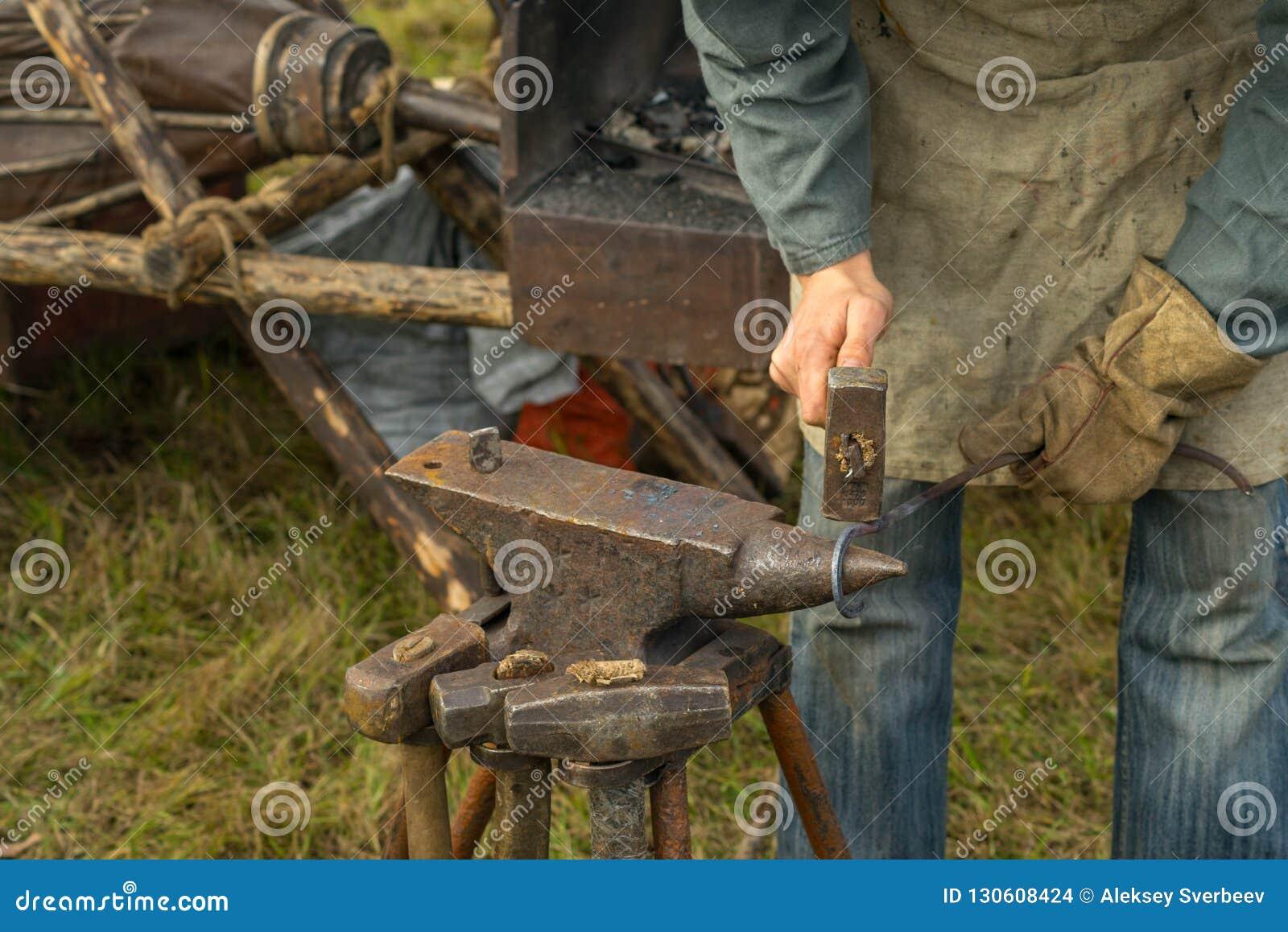 Кузнец работая на наковальне летом