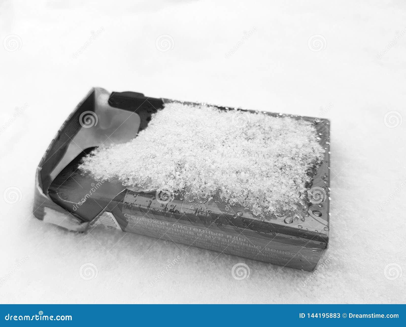 Курение - пакет сигареты в снеге в зиме