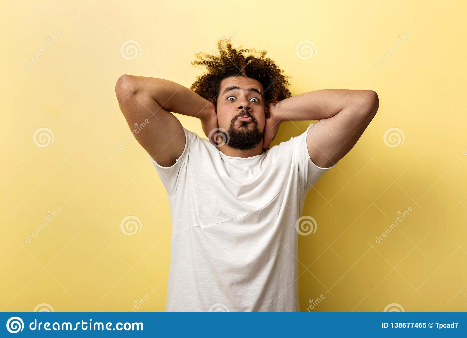 Курчавый возглавленный загоренный человек выглядит неистовым и держит его руки за его головой Губы закрыты в напряжении
