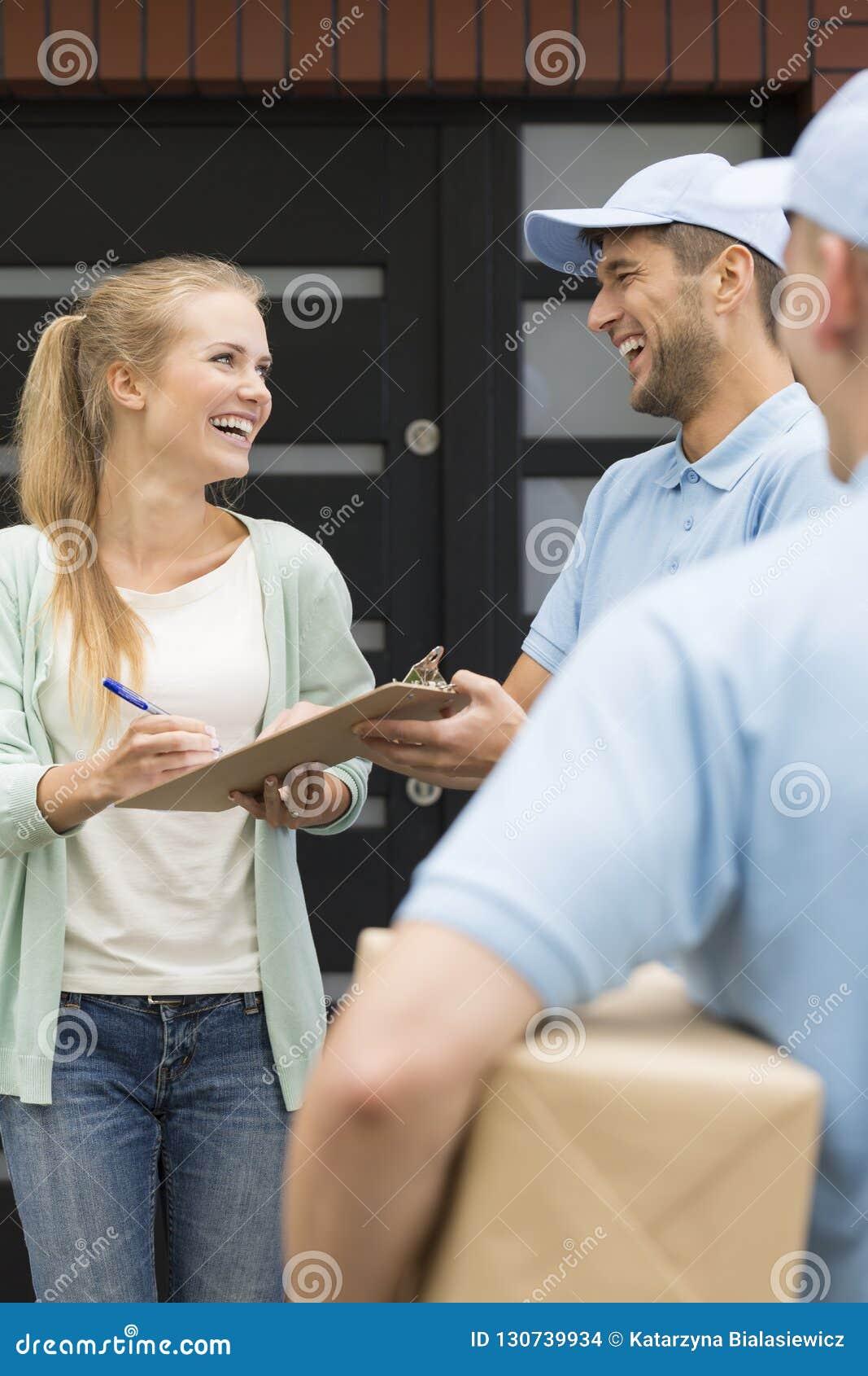 Курьеры давая пакеты счастливому получению подписания клиента