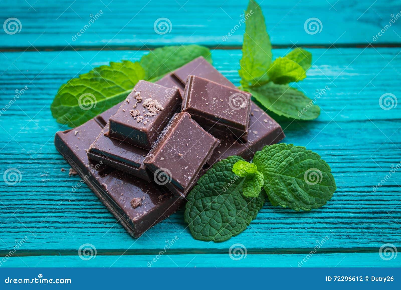 Download Куски шоколада с мятой на деревянной предпосылке Стоковое Фото - изображение насчитывающей черный, фармация: 72296612