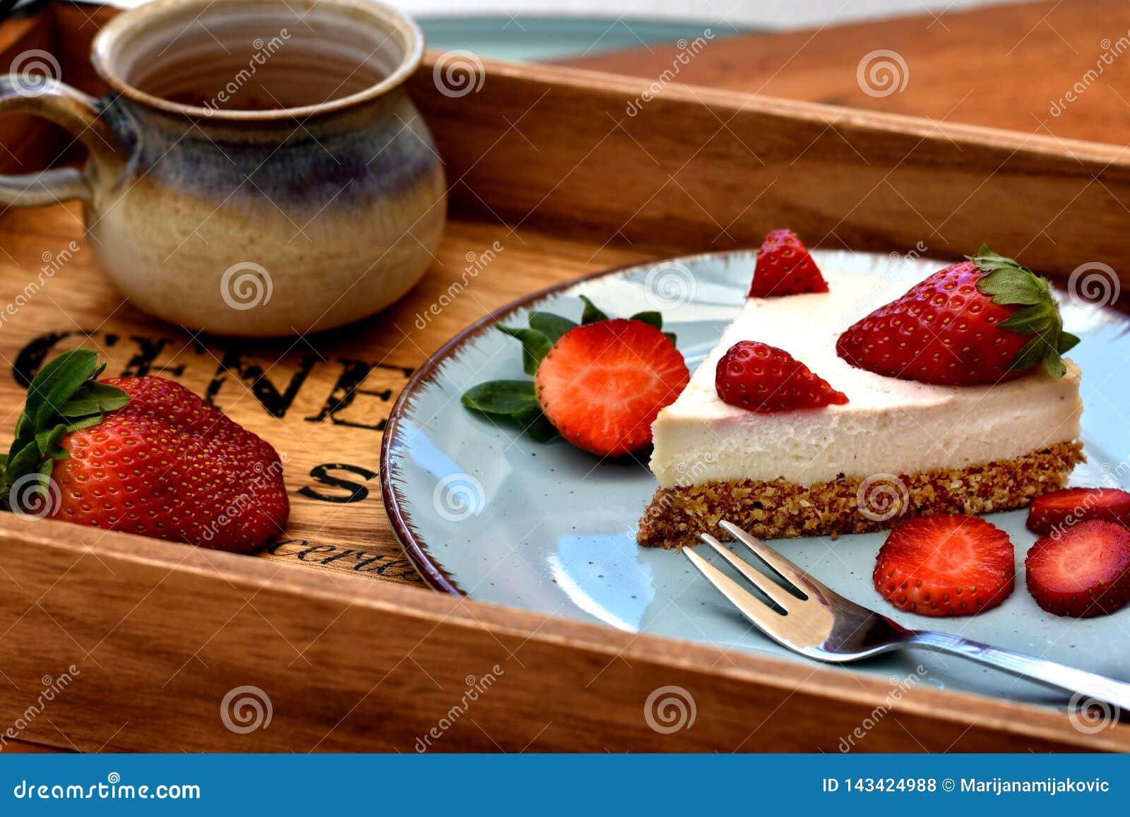Кусок сырцового белого торта клубники на голубой плите с чашкой кофе здоровая принципиальная схема завтрака