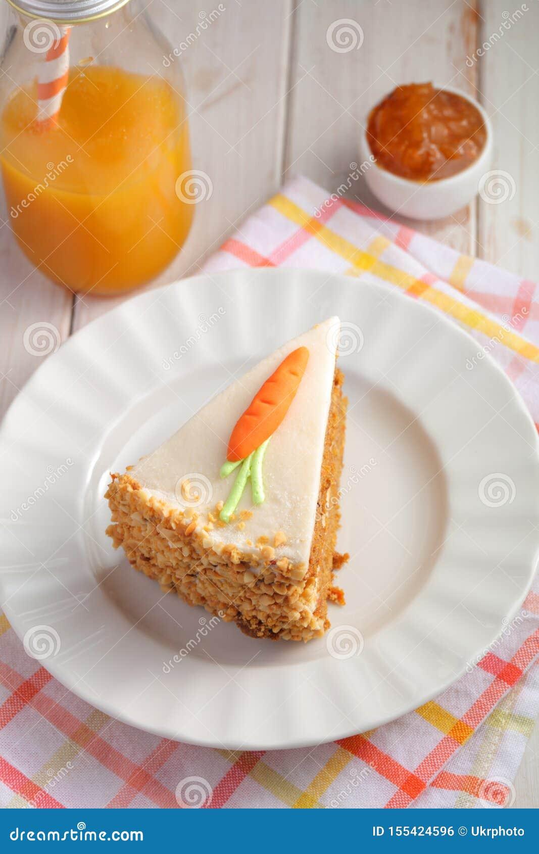 Кусок торта моркови пастельного de zanahoria с морковью замороженности и марципана на белой предпосылке с соком моркови