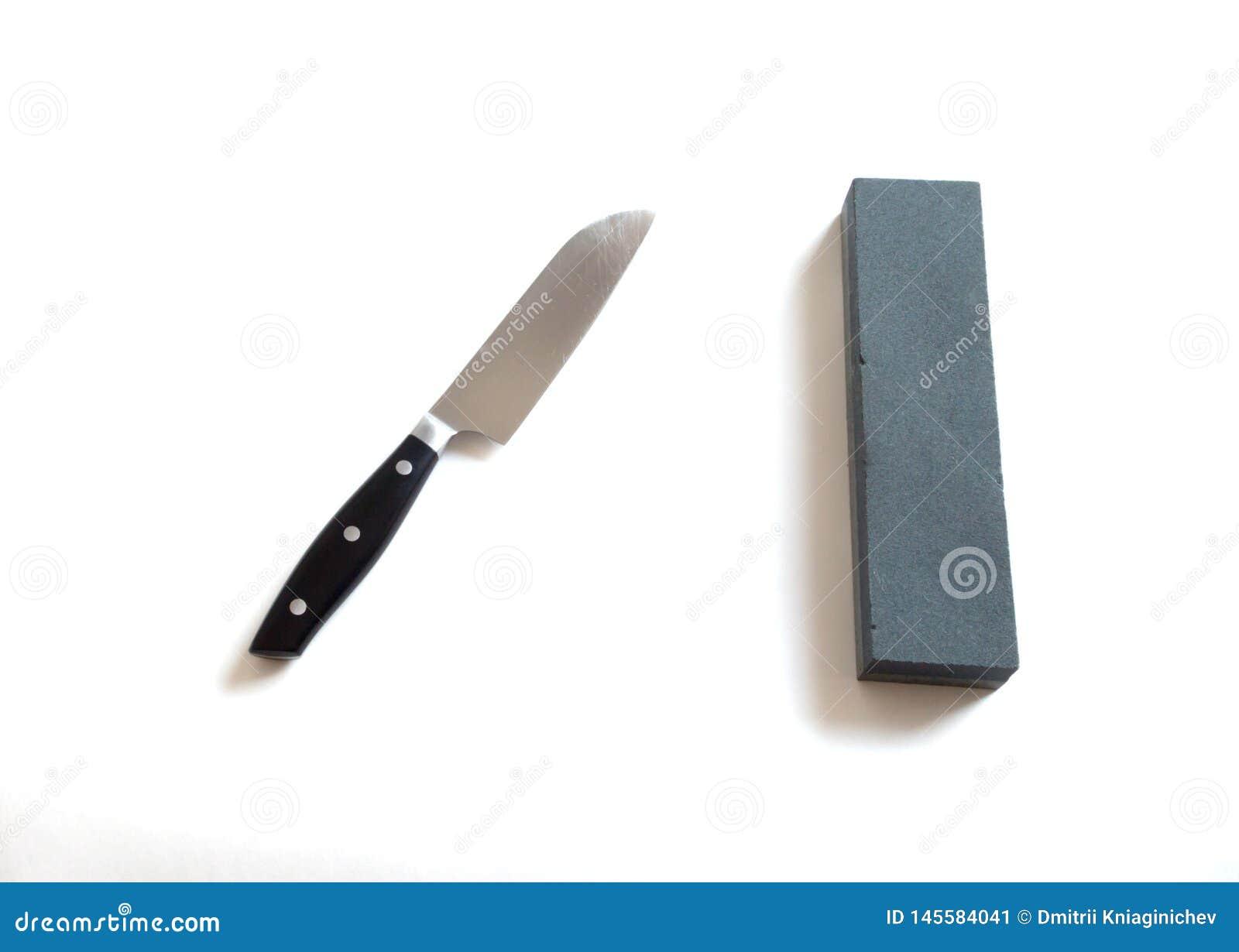 Кухонный нож и камень точить на белом фоновом изображении