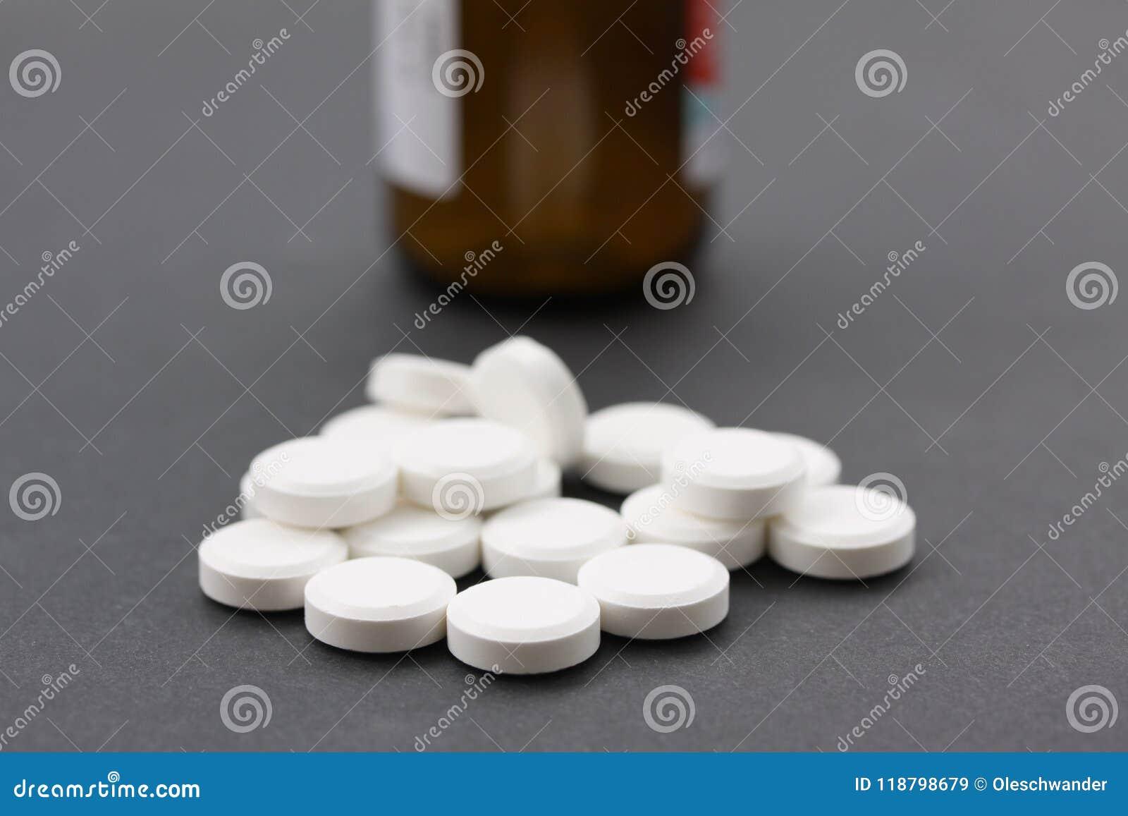 Куча белых пилюлек с коричневой бутылкой пилюльки в бутылке backgroundll иллюстрируя витамины или наркоманию к лекарствам закройт