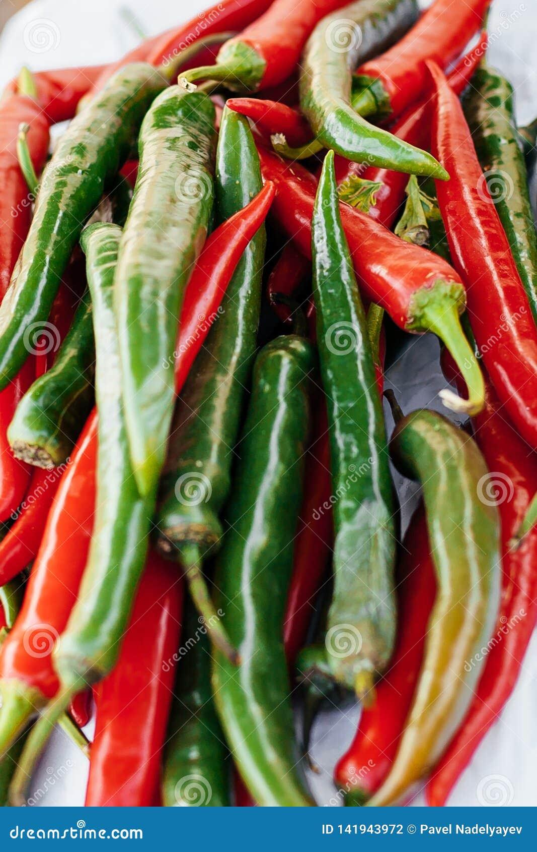 Куча красных и зеленых перцев горячих чилей закрывает вверх цветовой контраст